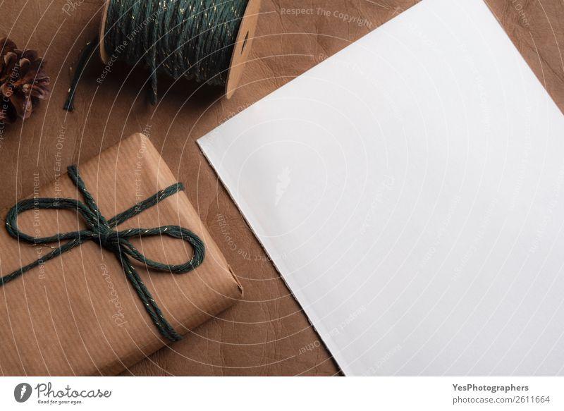 Leere Seite und ein Geschenk, das mit grüner Schnur gebunden ist. elegant Feste & Feiern Erntedankfest Weihnachten & Advent Geburtstag Leder retro braun