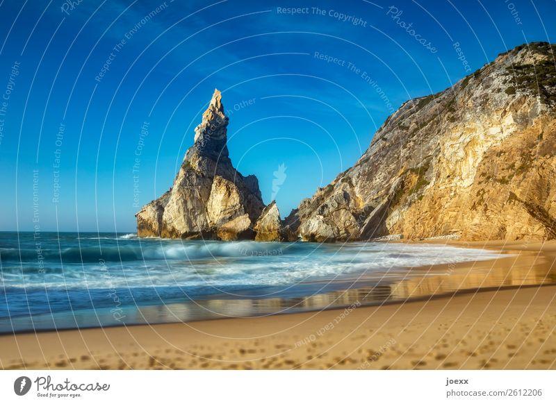 Großer spitzer Felsen an Küste mit Sandstrand mit leichten Wellen Felsenküste Meer Strand Himmel Landschaft Horizont Schönes Wetter Menschenleer Außenaufnahme