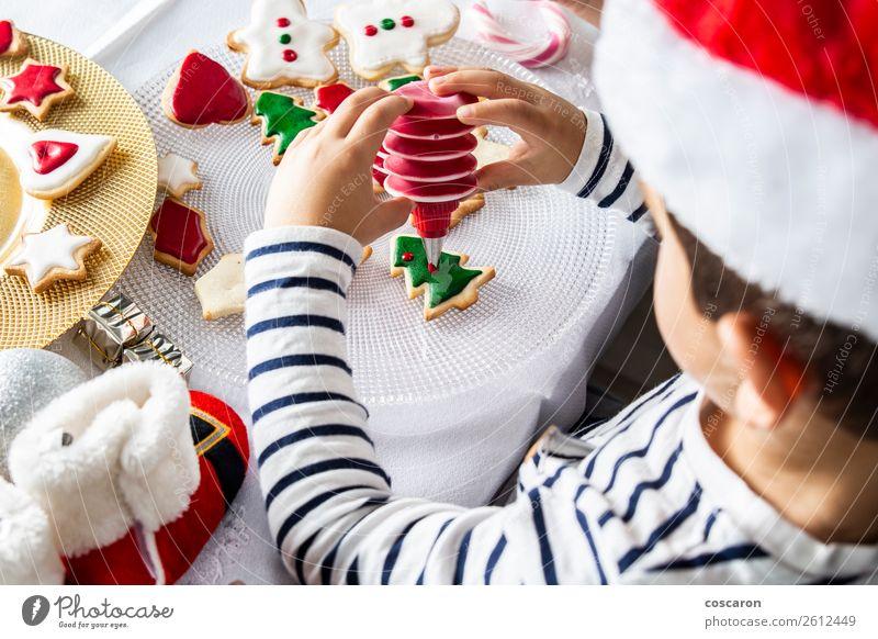 Kleines Kind schmückt Weihnachtsgebäck am Weihnachtstag Teigwaren Backwaren Dessert Süßwaren Freude Glück Freizeit & Hobby Dekoration & Verzierung Tisch Küche