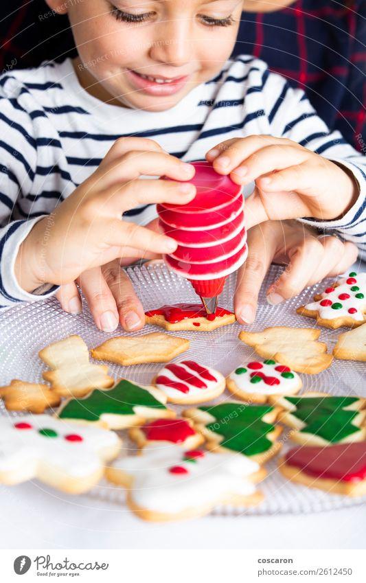 Kleines Kind schmückt Weihnachtsgebäck am Weihnachtstag Teigwaren Backwaren Freude Glück Dekoration & Verzierung Tisch Küche Feste & Feiern Weihnachten & Advent