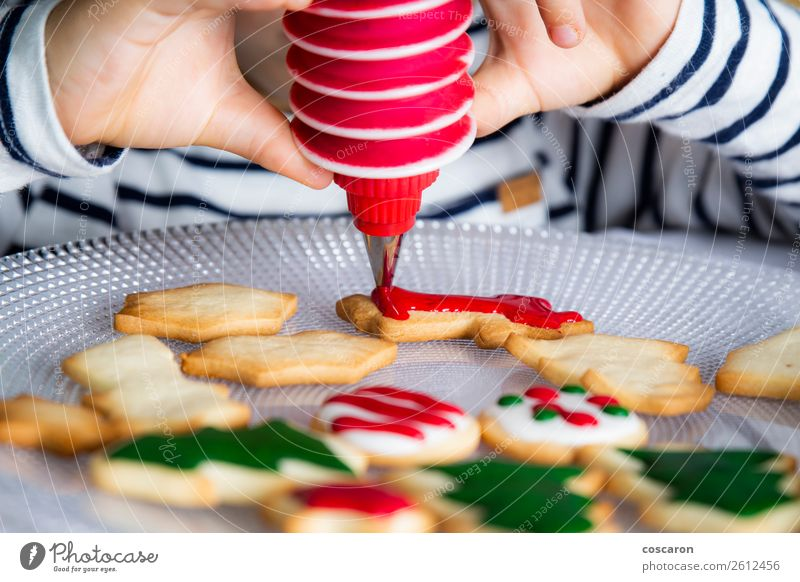Kleines Kind schmückt Weihnachtsgebäck am Weihnachtstag Teigwaren Backwaren Dessert Süßwaren Freude Glück Dekoration & Verzierung Tisch Küche Feste & Feiern