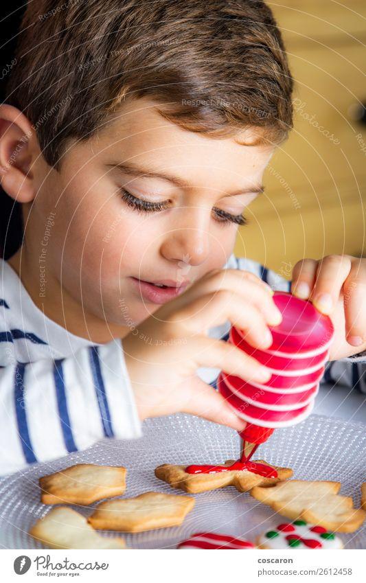 Kleines Kind schmückt Weihnachtsgebäck am Weihnachtstag Lebensmittel Teigwaren Backwaren Kuchen Dessert Lifestyle Freude Glück Freizeit & Hobby Kinderspiel
