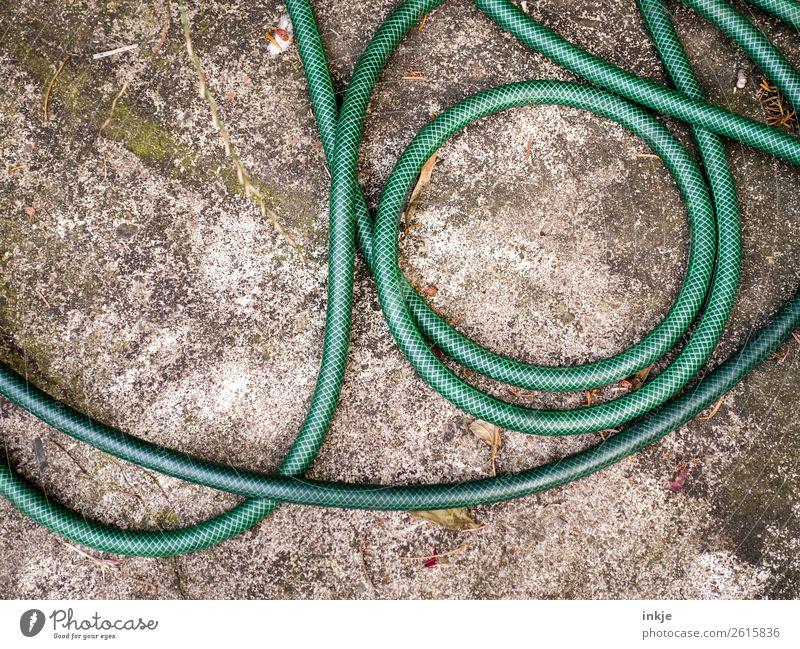 Grüner Gartenschlauch grün Häusliches Leben liegen Terrasse Windung unordentlich