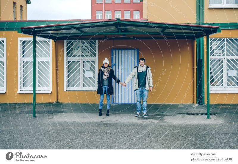 Ein Paar hält sich an den Händen unter dem Metalldach bei Regenwetter. Lifestyle schön Erholung Freizeit & Hobby Winter Mensch Frau Erwachsene Mann Freundschaft