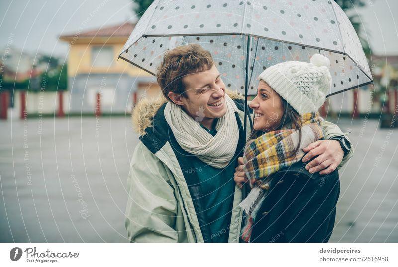 Junges Paar, das sich im Freien unter dem Regenschirm umarmt und lacht. Lifestyle Glück schön Winter Mensch Frau Erwachsene Mann Familie & Verwandtschaft Herbst
