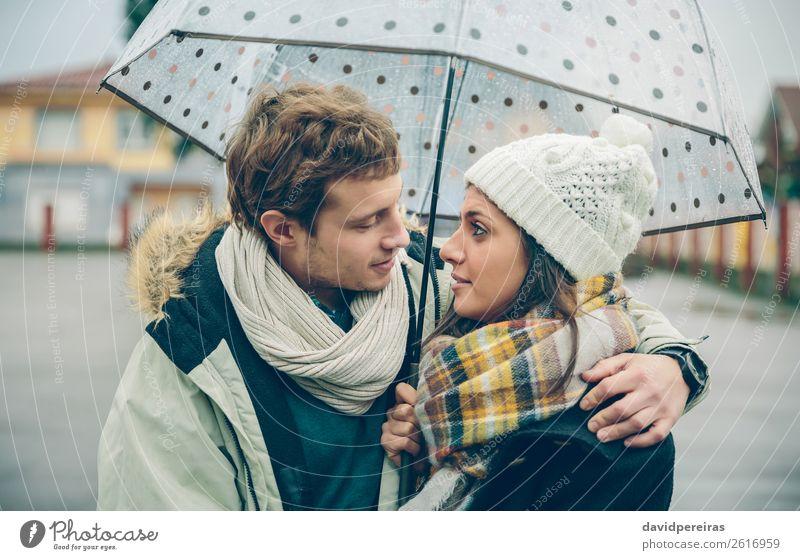 Junges Paar umarmt sich an einem regnerischen Herbsttag unter einem Regenschirm Lifestyle Glück schön Winter Mensch Frau Erwachsene Mann
