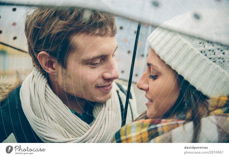 Junges Paar, das sich unter dem Regenschirm im Freien ansieht. Lifestyle Glück Winter Mensch Frau Erwachsene Mann Familie & Verwandtschaft Herbst Straße Schal
