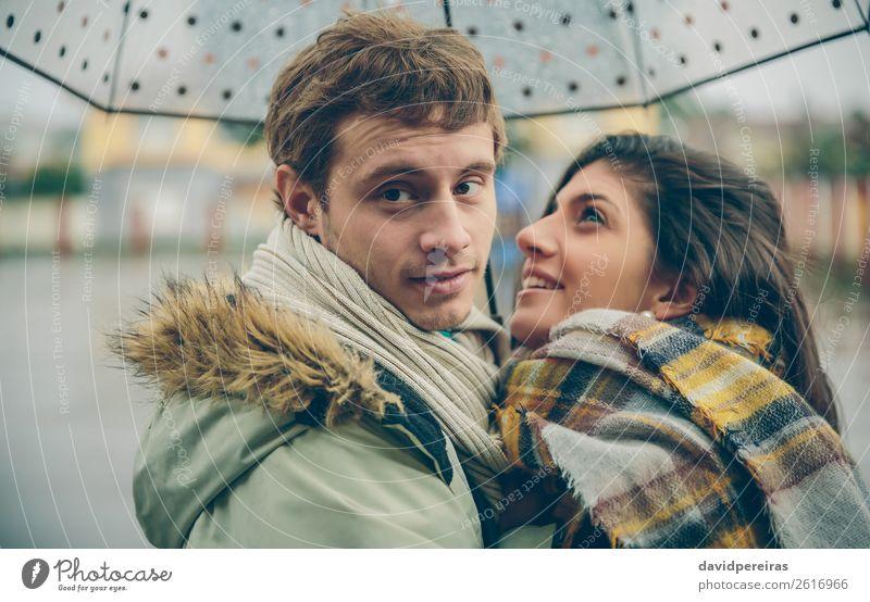 Ein glückliches Paar, das sich im Freien unter dem Regenschirm an regnerischen Tagen umarmt. Lifestyle Glück schön Winter Mensch Frau Erwachsene Mann