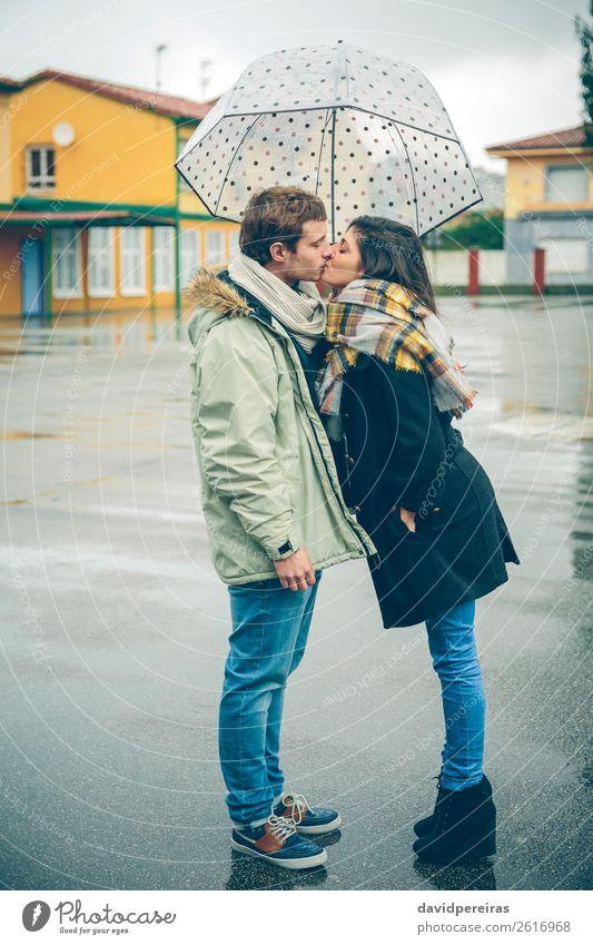 Junges Paar, das sich an einem regnerischen Tag unter dem Regenschirm im Freien küsst. Lifestyle schön Winter Mensch Frau Erwachsene Mann