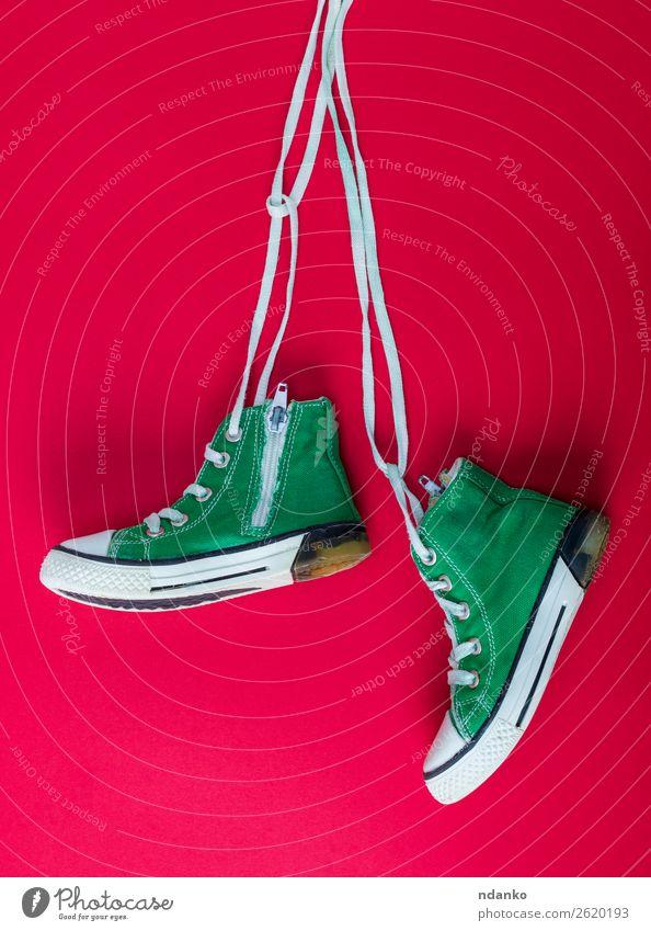 Paar getragene Textilsneakers mit weißen Schnürsenkeln Lifestyle Stil Sport Joggen Seil Mode Bekleidung Schuhe Turnschuh Fitness hängen trendy modern retro grün