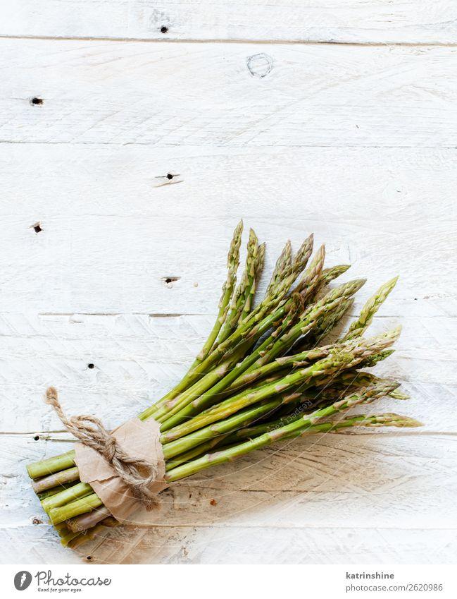 Frische rohe Spargelstangen auf einem weißen Tisch Gemüse Ernährung Abendessen Vegetarische Ernährung Diät frisch oben grün schwarz rustikal saisonbedingt Speer