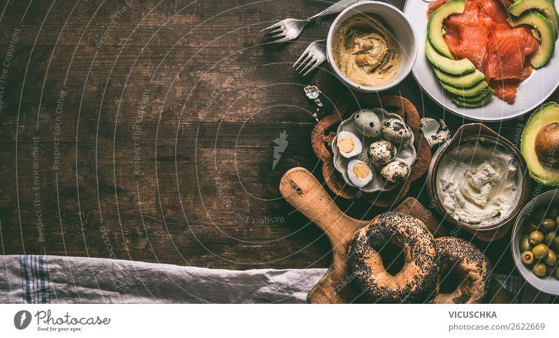Hausgemachte Frühstückszubereitung mit Bagel-Brot, Lachs, Avocado, Frischkäse, Hummus und gekochten Wachteleier auf dunklem, rustikalem Holzgrund, Draufsicht. Kopierfläche für Ihr Design, Banner