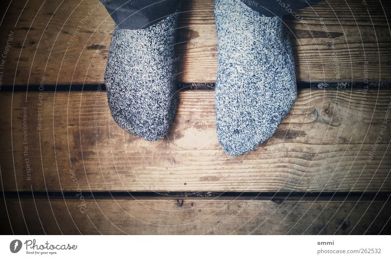 white noise Fuß 1 Mensch Strümpfe Holz sitzen alt authentisch einfach trist braun grau schwarz weiß ruhig stagnierend Holzfußboden Vignettierung Farbfoto