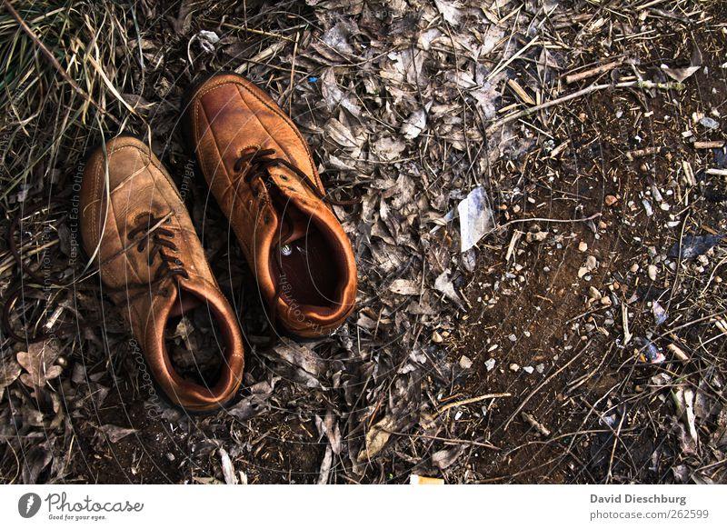 Schuhe des barfüßigen Jägers Leder braun Schuhbänder Fundstück Boden Erde alt Lederschuhe ruhig Stillleben paarweise Farbfoto Außenaufnahme Menschenleer Tag