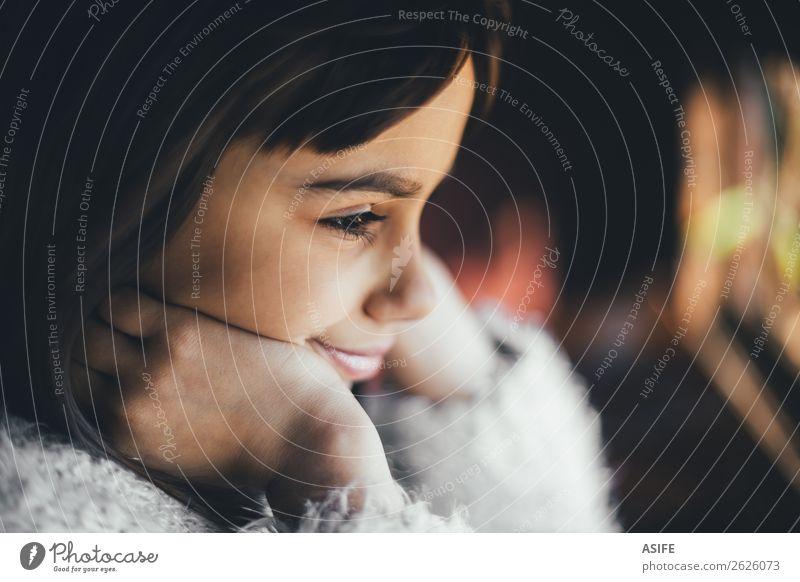 Verträumtes und glückliches kleines Mädchen, das durch das Fenster schaut. Geringe Tiefenschärfe Freude Glück schön Winter Kind Kindheit Herbst Wärme brünett