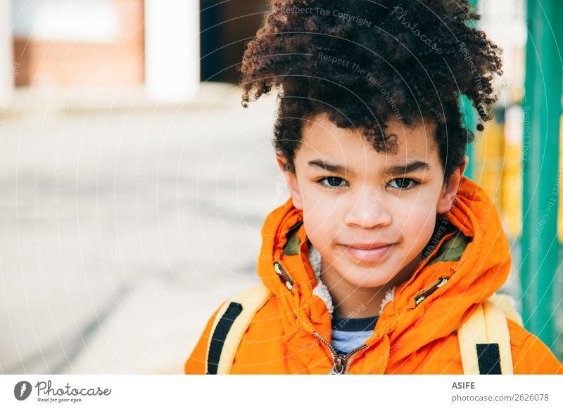 Kleiner Schuljunge am Eingang der Schule Glück Winter Kind Junge Herbst Mantel Lächeln klein gelb schwarz Schulkind Rucksack Schüler gutaussehend Afrikanisch