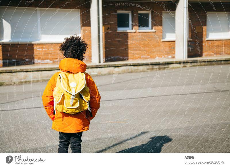Kleiner Schuljunge am Eingang der Schule Winter Kind Junge Herbst Mantel klein gelb schwarz Schulkind Rucksack Schüler gutaussehend Afrikanisch Nachkomme