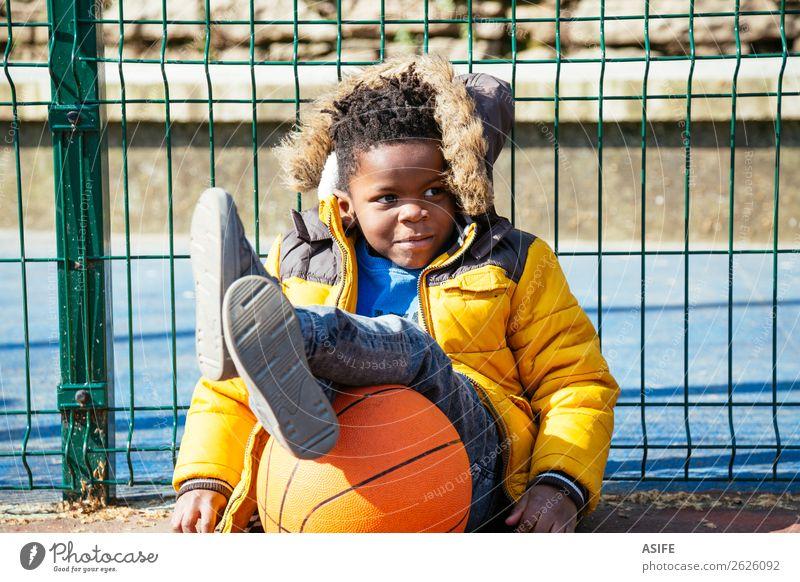 Lustiger kleiner Junge ruht sich aus, nachdem er Basketball gespielt hat. Freude Glück Erholung Freizeit & Hobby Spielen Winter Sport Kind Schule Kindheit