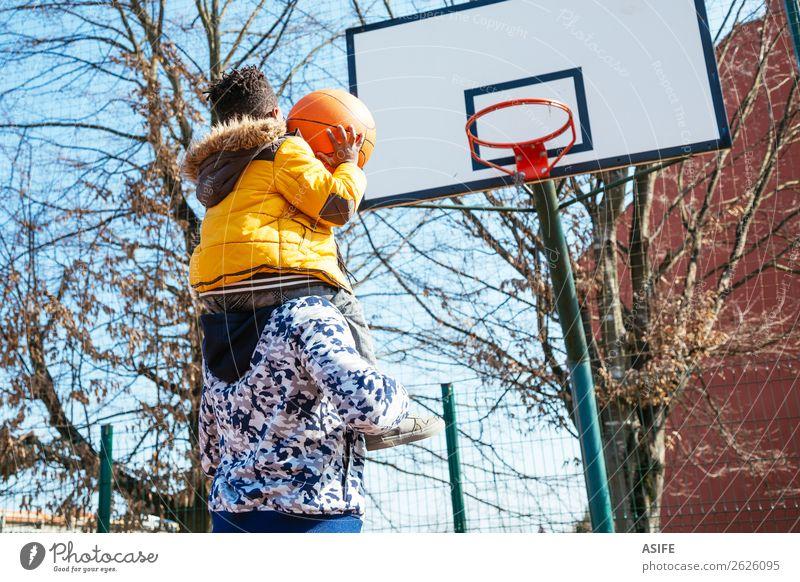 Kleiner Junge auf daddy´s Schulter spielt Basketball Freude Glück Erholung Freizeit & Hobby Spielen Winter Sport Schule Eltern Erwachsene Vater
