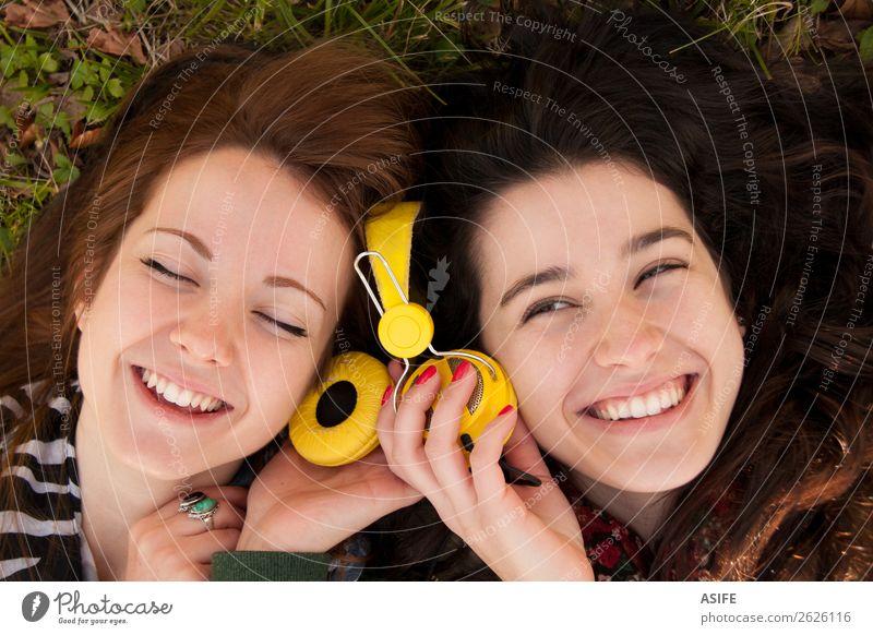 Teenagermädchen teilen Musik, die im Gras liegt. Freude schön Winter Headset Mensch Frau Erwachsene Freundschaft Jugendliche Herbst Blatt brünett blond