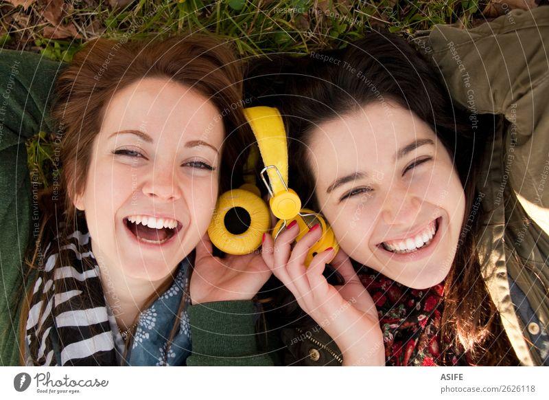 Zwei glückliche Teenager-Mädchen liegen auf dem Gras und teilen Kopfhörer, um Musik zu hören Freude schön Winter Headset Mensch Frau Erwachsene Freundschaft