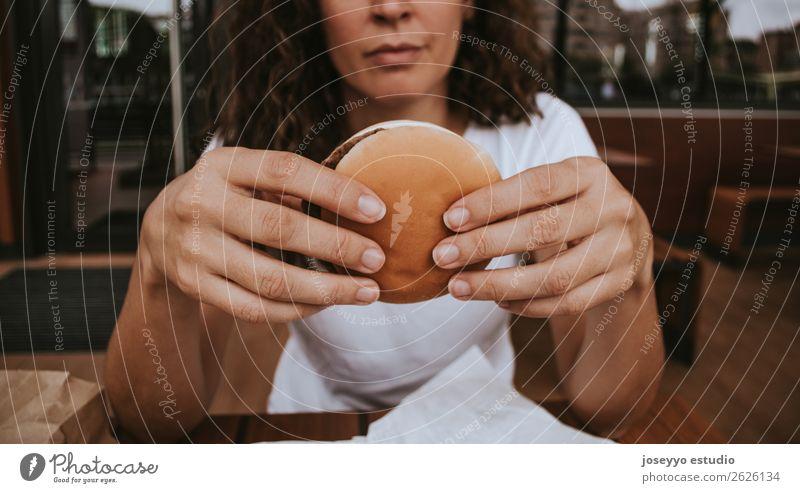 Junges Mädchen mit Fastfood-Burger in der Hand Lebensmittel Brot Mittagessen Lifestyle Stil schön Mensch Frau Erwachsene Straße Mode Fröhlichkeit lecker