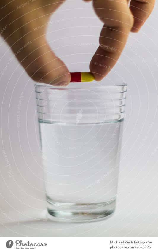 Männer geben eine rot-gelbe Pille in einem Glas Wasser. Schalen & Schüsseln Behandlung Krankheit Medikament Wissenschaften Hand Holz blau rosa weiß Farbe zeigen