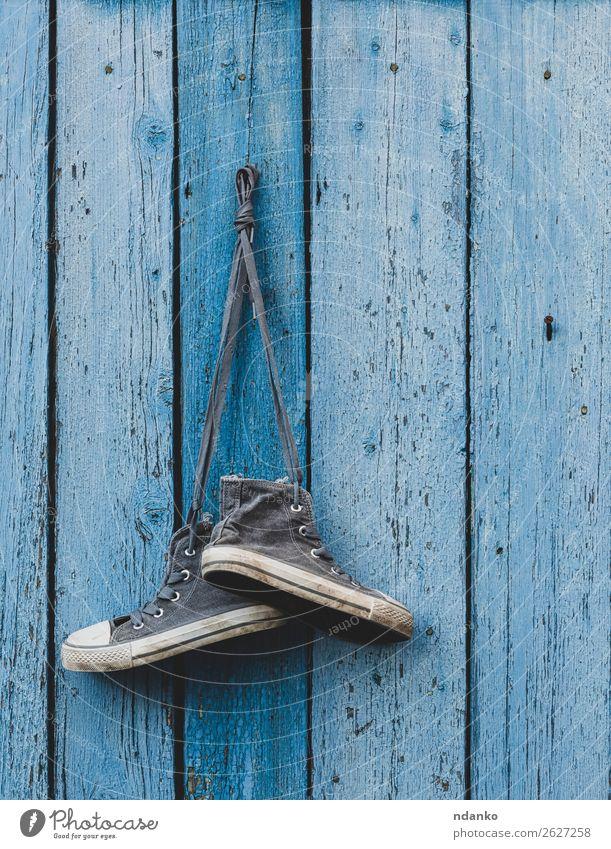 sehr alte textile Sneakers, die an einem Nagel hängen. Lifestyle Sport Joggen Mode Bekleidung Schuhe Turnschuh Holz Fitness dreckig trendy modern blau Idee