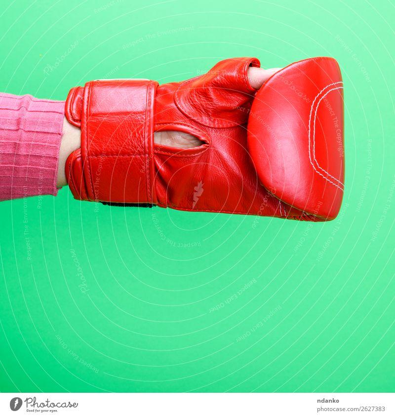 Hand trägt einen roten Leder-Boxhandschuh auf grünem Hintergrund. Sport Frau Erwachsene Handschuhe Fitness Schutz Farbe Konkurrenz Kreativität Schlag zeigen