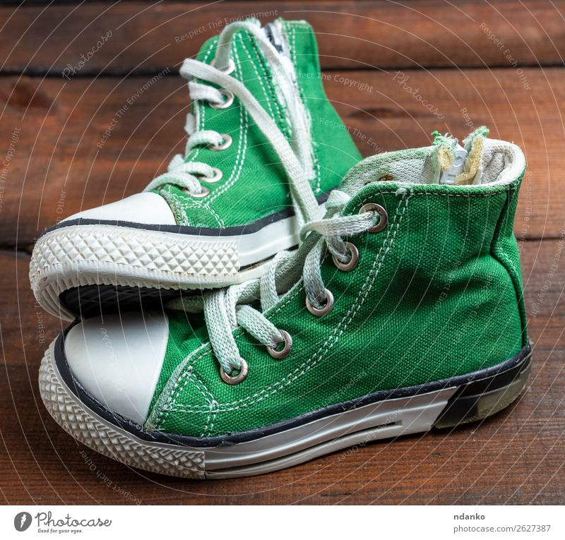 Paar getragene grüne Textilsneakers Lifestyle Stil Design Sport Joggen Mode Bekleidung Schuhe Turnschuh Holz Rost alt Fitness dreckig trendy klein modern