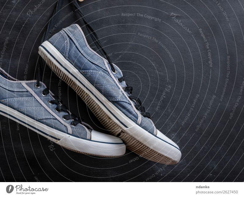 Paar textile blaue Turnschuhe hängen an einem String. Lifestyle Stil Sport Joggen Mode Bekleidung Schuhe Holz Rost alt Fitness dreckig trendy modern retro
