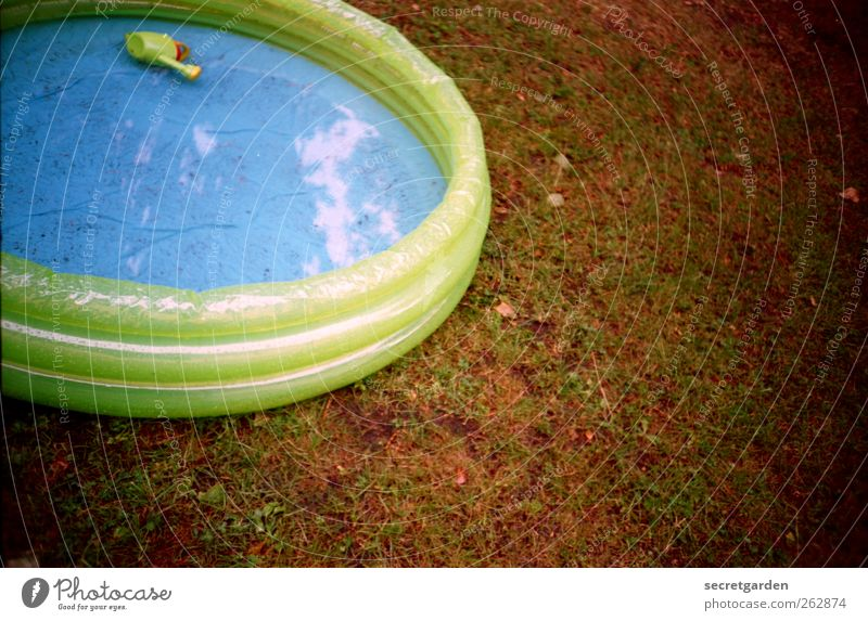 sonnenbaden. Gras Wiese Spielzeug Gießkanne rund blau braun grün Planschbecken Wasser nass Gummi kinderlos aufblasbar Kunststoff analog Farbfoto mehrfarbig