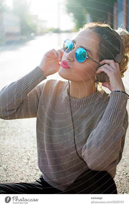 Junge Frau beim Musikhören auf der Straße Lifestyle Freude Wellness Leben Jugendliche Jugendkultur Musik hören Musiker Mode Accessoire Sonnenbrille Kopfhörer