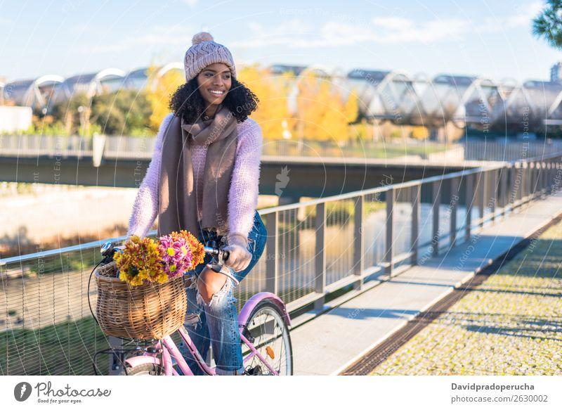 Schwarze junge Frau auf einem Oldtimer-Fahrrad altehrwürdig Korb Mädchen Person gemischter Abstammung schön retro Blume Glück Blumenstrauß Winter Herbst