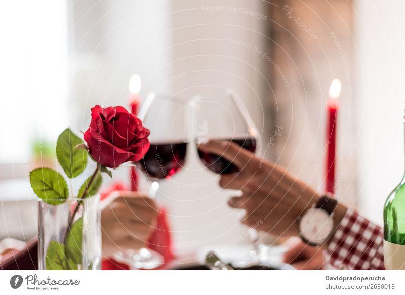 Junges glückliches Paar, das den Valentinstag mit einem Abendessen zu Hause feiert, Wein trinkt und prost. Alkohol schön Freund Gast Zuprosten trinken Essen