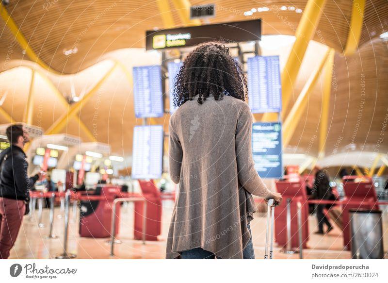 Black Woman betrachtet das Fahrplanauskunftstafel im Flughafen mit einem Koffer. Zeitplanung Anzeige Panel Mensch Etage Holzplatte international Frau