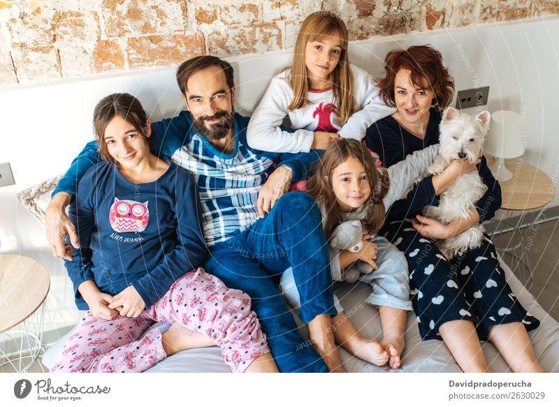 Ein erwachsenes Paar entspannte sich zu Hause im Bett mit ihren vier kleinen Töchtern und dem Hund. Familie & Verwandtschaft Schlafzimmer Ehefrau Ehemann
