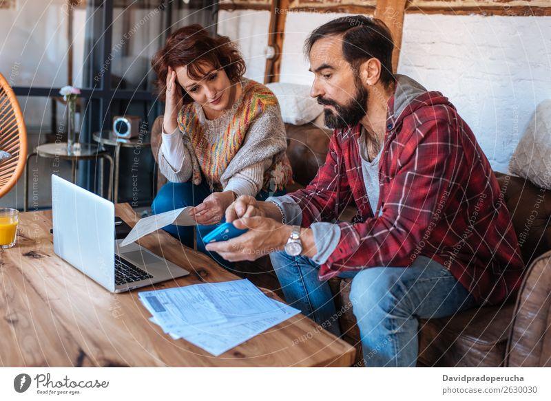 Ältere Paare, die zu Hause sitzen und ihre Finanzprobleme betrachten. reif Erwachsene Partnerschaft Wut Geldscheine 50's alt Kaukasier Ärger kämpfen Gutschein