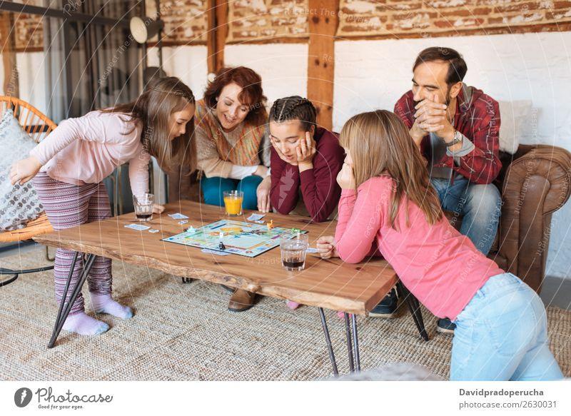 Glückliche Familie zu Hause auf der Couch mit klassischen Tischspielen Familie & Verwandtschaft Spielen Holzplatte Vater heimwärts Mensch Schwestern Kaukasier