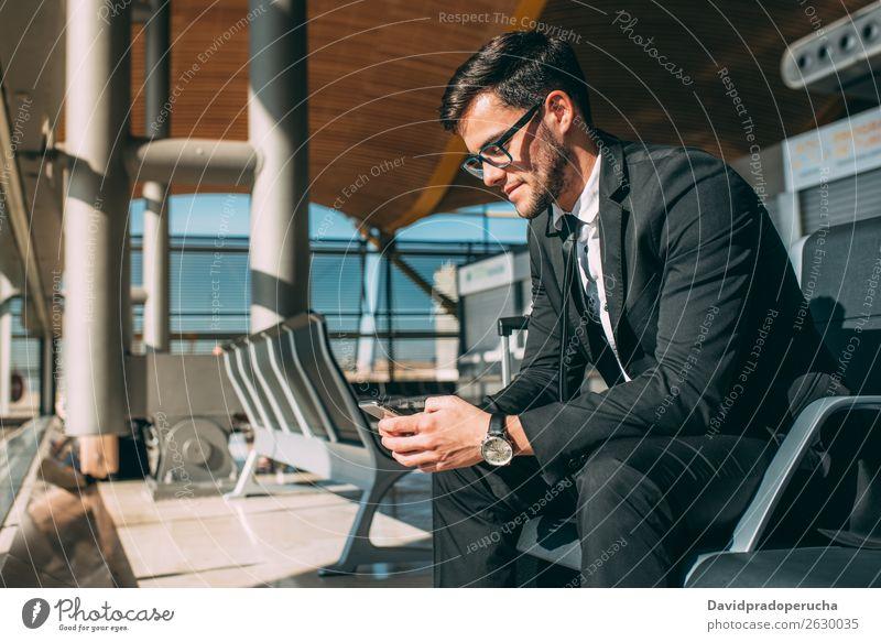 Junger Geschäftsmann am Telefon mit dem Koffer am Flughafen, der auf den Flug wartet. Mann Ferien & Urlaub & Reisen Mobile Mitteilung Technik & Technologie