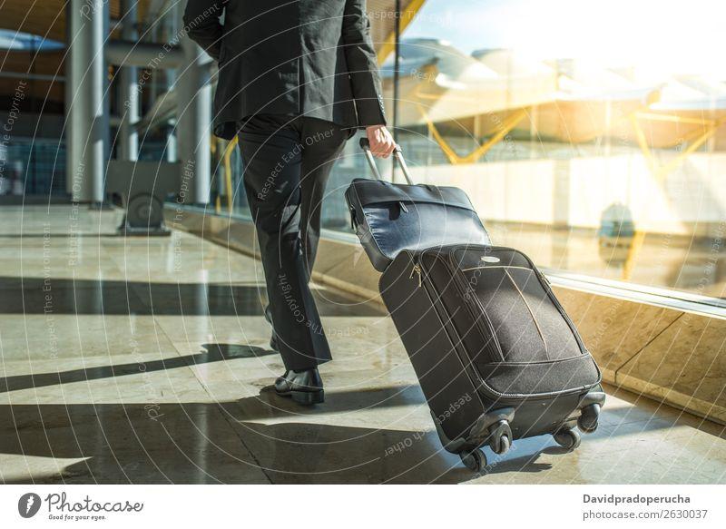 Geschäftsmann mit Rücken und Beinen, der mit Gepäck am Flughafen unterwegs ist. laufen Schritt Fenster Abflughalle Anzug Mann Ferien & Urlaub & Reisen Business