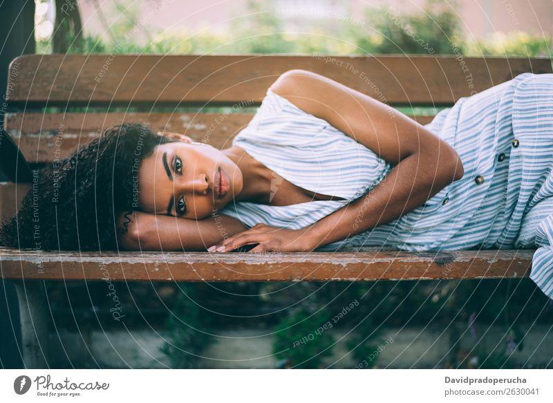 Schöne junge schwarze Frau, die sich auf einem Stuhl in einem Park niederlässt. Beautyfotografie Nahaufnahme Porträt multiethnisch Afrikanisch