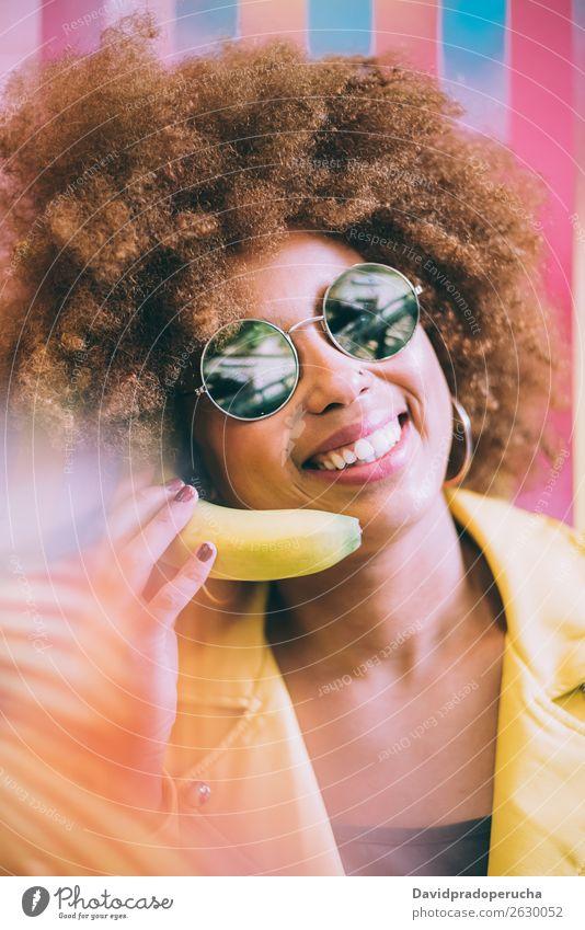 Überraschte Mixed-Race-Frau in einer bunten Kunstwerk-Hintergrundmauer, die mit einer Banane spielt. gemischt Nahaufnahme Porträt schwarz heiter gelb Mobile