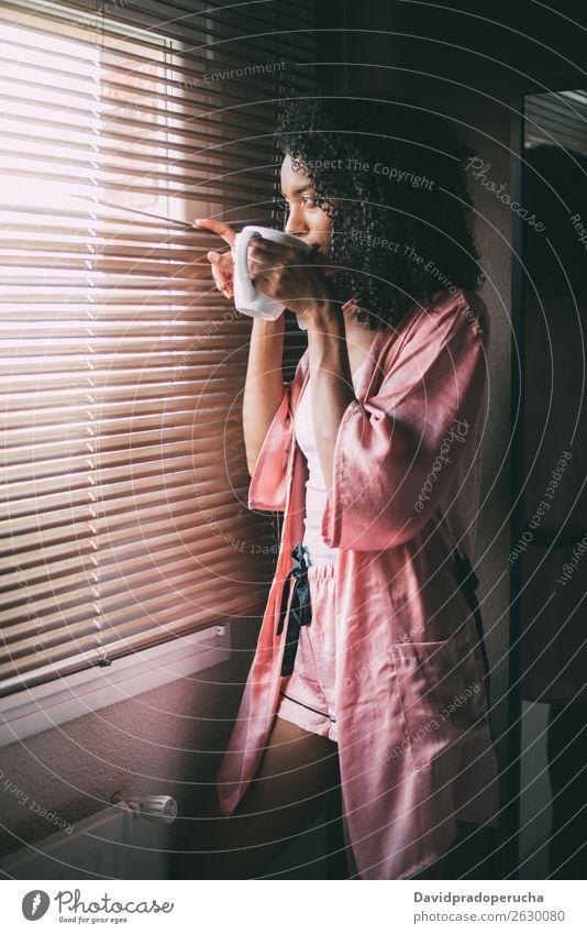 hübsche schwarze Frau am Fenster stehend mit einer Tasse Kaffee Tee hintergrundbeleuchtet Schlafzimmer Afro-Look Afroamerikaner genießen trinken Jugendliche