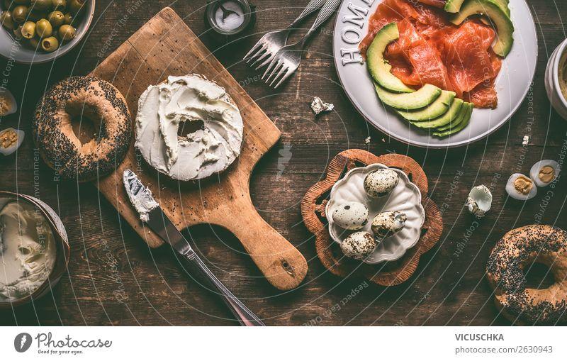 Frühstück mit Bagel, Frischkäse , Lachs und Avokado Lebensmittel Fisch Käse Gemüse Ernährung Bioprodukte Geschirr Teller Stil Design Gesunde Ernährung