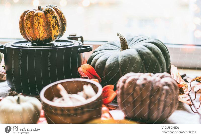 Kochtopf und Kürbisse auf dem Küchentisch am Fenster Lebensmittel Gemüse Ernährung Topf Design Gesunde Ernährung Winter Häusliches Leben Herbst Hintergrundbild