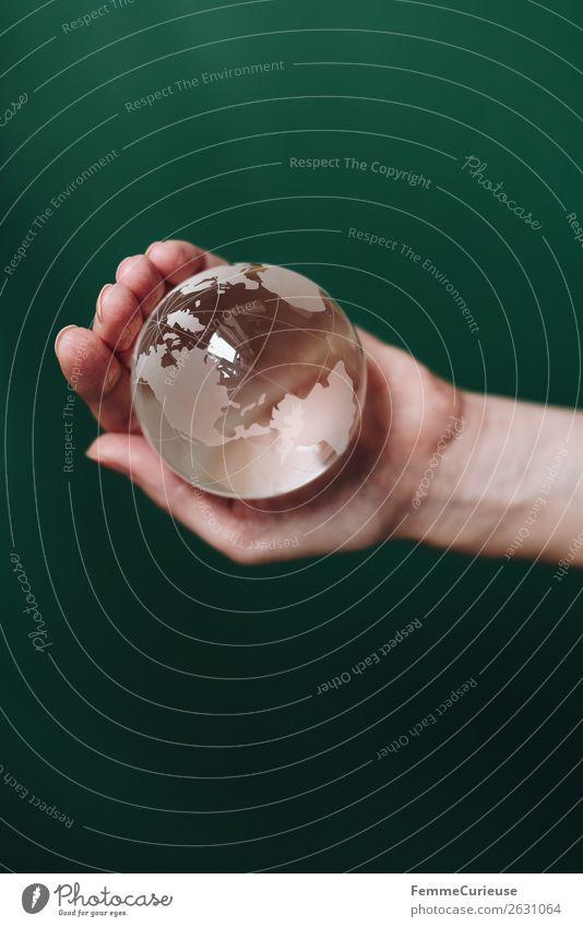 Hand with transparent globe in front of green background Natur Horizont Globus Erde durchsichtig festhalten dunkelgrün Nordamerika Südamerika Amerika Pazifik