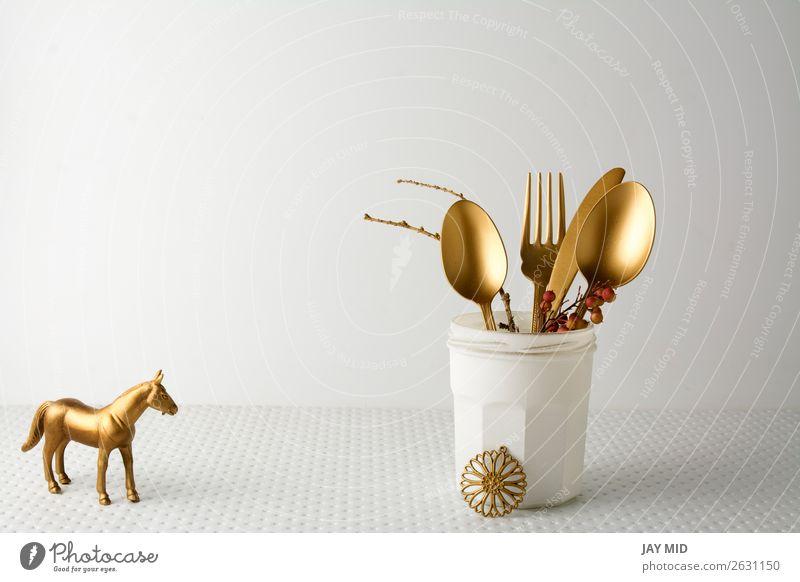 Festliches goldenes Besteckmesser und Gabellöffel in einer weißen Flasche. Mittagessen Abendessen Löffel elegant Design Dekoration & Verzierung Tisch Küche