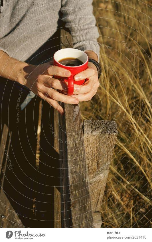 Mann hält eine Tasse Kaffee auf einer Holzbank. Frühstück Getränk trinken Heißgetränk Kakao Tee Lifestyle Gesundheit Gesunde Ernährung Wellness Wohlgefühl