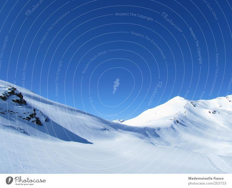 Berggrat im Schnee Wolkenloser Himmel Sonnenlicht Winter Schönes Wetter Felsen Alpen Berge u. Gebirge blau weiß Abenteuer anstrengen Zufriedenheit Bewegung